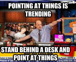 pointing at things is trending stand behind a desk and point -
